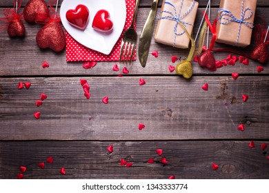 Border from red  decorative hearts, boxes with presents and plate, cultery on vintage wooden background. Selective focus.  Flat lay. Place for text.