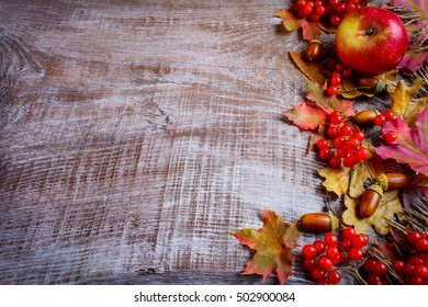 Border of ripe fruits and fall leaves on the dark wooden background. Thanksgiving greeting card with seasonal fruits.  Copy space