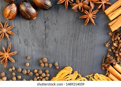 Border of spices on wooden background. Cinnamon, nutmeg, cloves, allspice, star anise.