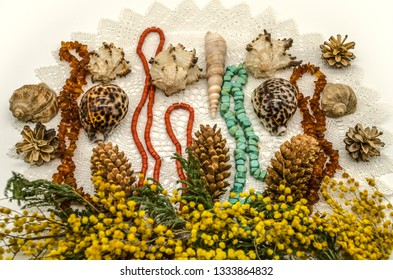A border of sprigs of yellow Mimosa  with pine cones, sea shells and beads of amber, turquoise and red coral on knitted of white yarn laced napkin