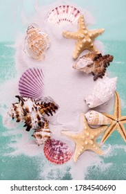 Border of Starfishes and seashells on dune sand and aquamarine color background. Top view marine Vacation backdrop.