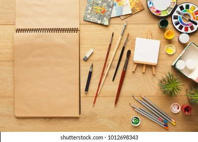 Border of various stationery for art, top view. Light wooden desktop with pencils, open colors, brushes and yellow paper of sketch-book with copy space for text. Studying and creative background