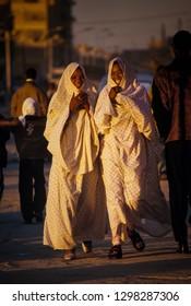 BORDJ EL HAOUAS, ALGERIA - JANUARY 16, 2002: two unknown women at sunset walking on the sidewalk