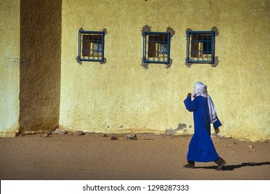 BORDJ EL HAOUAS, ALGERIA - JANUARY 16, 2002: Unknown man from the Touareg tribe crosses the main road in the middle of the desert