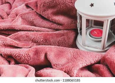 Bordo color plaid on the sofa, white pillow and lantern with a candle. Concept of home cosiness, lazy sunday, Christmas mood, cosy and soft winter background, flat lay, still life