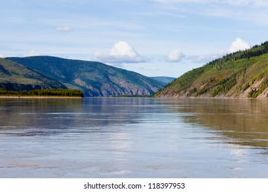 Boreal forest hills at river bank of Yukon River, Yukon Territory, Canada, near Dawson City forming a beautiful northern riverscape.
