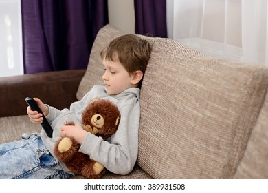 Bored 7 year old boy child sitting on the sofa and watching tv. Hugs his favorite teddy bear and changing channels by remote control.