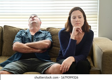 Bored adult couple forced to stay at home as the pandemic coronavirus (COVID-19) forces many people to stay at home because new government policies. Real people. Copy space