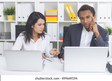 Bored African American guy is looking at computer screen while listening to his boss's critique. Concept of being wrong and not acknowledging it