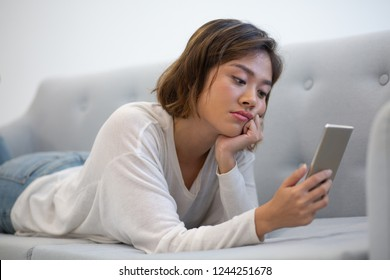 Bored Asian phone user browsing internet. Young woman in casual lying on couch, leaning cheek on hand and using smartphone. Boredom concept