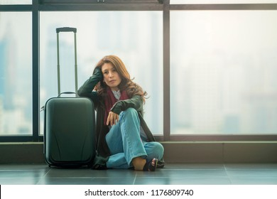 Bored asian woman with suitcase in airport waiting room upset girl traveling along waiting for the next flight with copy space.