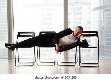 Bored attractive man in stylish business suit lying relaxed on office chairs in a row, resume in hand. Job applicant tired of long waiting for his turn on interview. Post candidate in reception room