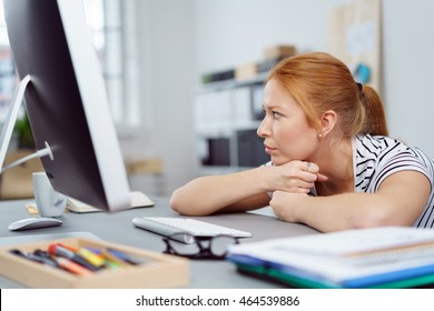 Bored attractive young business woman at work leaning her chin on her hands staring off to the side with a serious preoccupied expression