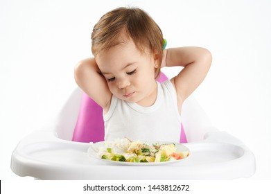 Bored baby girl with food isolated on white studio background