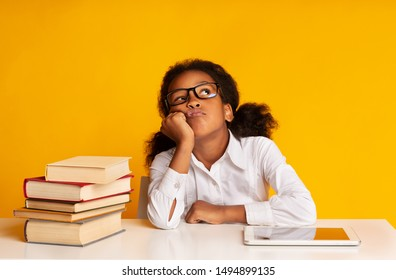Bored Black School Girl Sitting Between Tablet Computer And Book Stack On Yellow Background In Studio. Boring Homework Concept