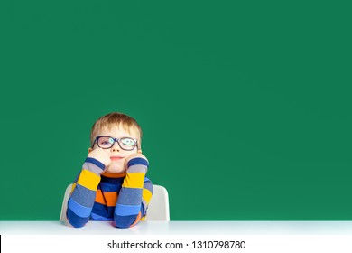 A bored boy with glasses is sitting at the table. Copy space.