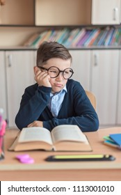 bored boy with glasses and uniform at school desk, concept of children's school emotions