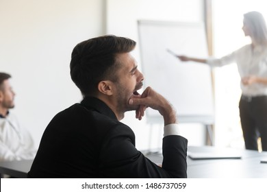 Bored business man feel tired sleepy yawning fall asleep during corporate presentation meeting training, lazy unmotivated worker distracted want to sleep at work during boring office conference event