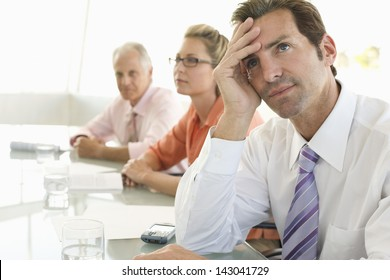 Bored businessman with colleagues in background at conference table