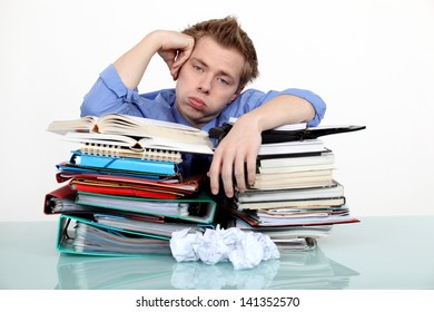 Bored businessman leaning on a stack of files