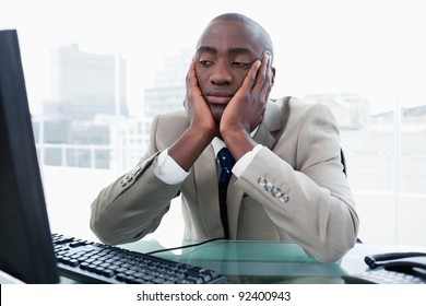 Bored businessman looking at his computer in his office