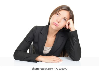 Bored businesspeople: woman sitting at desk staring bored upwards. Beautiful young multiethnic asian caucasian business woman isolated on white background.
