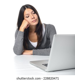 Bored businesswoman sitting at her desk with her head resting on her fist staring at her laptop computer with a resigned expression, on white
