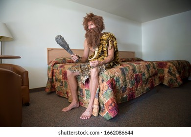 Bored caveman sitting indoors on the edge of a bed with a colorful bedspread in an anonymous cheap motel room