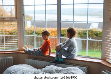 bored children sitting on sill at window at quarantine time