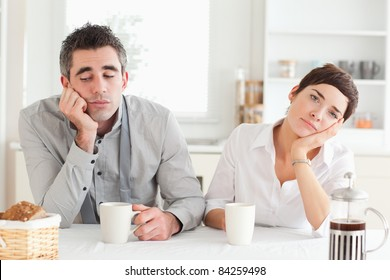 Bored couple drinking coffee in a kitchen