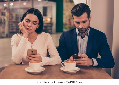Bored couple sitting in a cafe holding phones