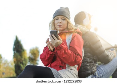 bored couple. young girl using phone ignoring boyfriend. concept of technology, cell phone addiction and  break up of a love story