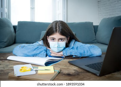 Bored and depressed teenager girl with face mask on laptop studying at home in online education class as high school remain closed due to New COVID-19 lockdown or forecast weather conditions.