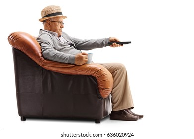 Bored elderly man holding a cup and a remote sitting in an armchair and watching television isolated on white background