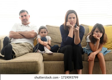 Bored family in self quarantine sitting on a couch in home living room staring at TV screen.
