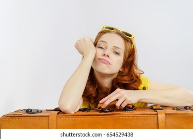 Bored frustrated young woman leaning on her brown leather suitcase while traveling on summer vacation during a delay or lay over