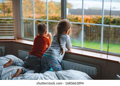 bored girl and boy looking through window staying at quarantine