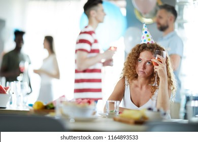 Bored girl with glass of drink sitting by table at birthday party while her friends communicating near by