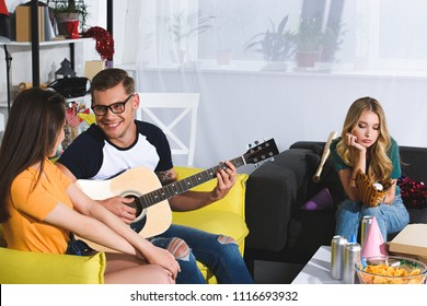 bored girl holding baseball ball with glove while smiling man playing guitar and looking at beautiful woman