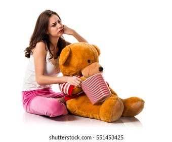 Bored girl with pajamas holding a bowl of popcorns and playing with a stuffed animal