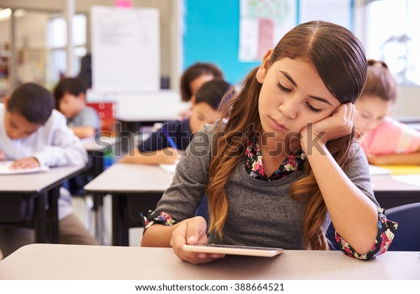 Bored girl reading tablet in elementary school class
