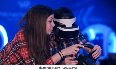 Bored girl trying to distract her boyfriend from playing virtual reality racing game