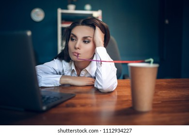 Bored girl watching something on her laptop in office room. Uninterested business lady drinkin carelessly from coloured straw from disposable brown coffee cup while looking into computer.