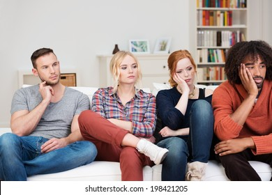 Bored group of multiracial friends relaxing at home sitting in a row on a comfortable sofa watching something off screen to the right with glum expressions