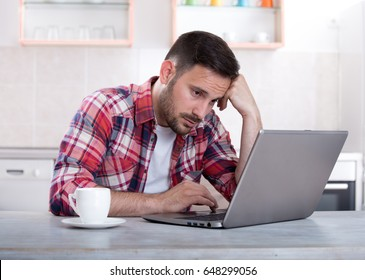 Bored handsome young man sitting at dining table and looking at laptop