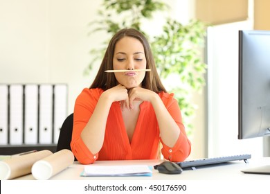 Bored or incompetent businesswoman playing with a pencil in a desktop at office
