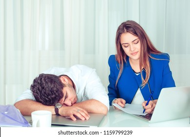 Bored lazy man sleeping at table with smart creative woman working sitting near at table in office living room at home. Overworking late hours working night shift different workers concept.