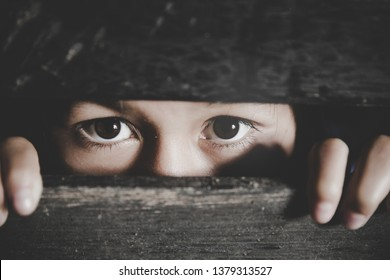 Bored little girl, Frightened child is spying through a wooden fence. Scared child girl. Human emotion, facial expression. Sad kid outdoors.