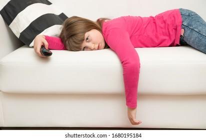 ein langweiliges Mädchen, das auf dem Sofa liegt, sieht während der Coronavirus-Quarantäne fern