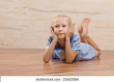 Bored little girl lying on the wooden floor with her bare feet up in the air and her chin resting on her hands as she stares ahead of her with a fed up expression